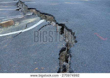 Crack On Asphault Rural Road. Damaged Collapsed Street