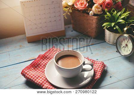 Cup Of Coffee With Desktop Calendar 2019,clock And Pot Of Rose Flower On Blue Wooden Desk.calendar F