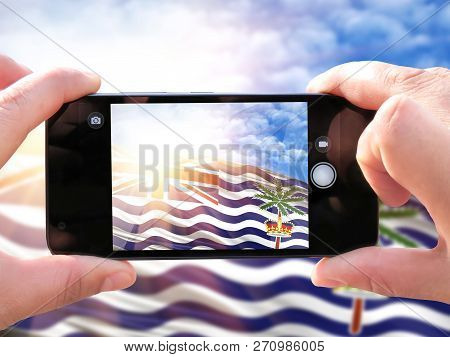 The Hands Of Men Make A Phone Photograph Of The Flag Of British Territory In The Indian Ocean