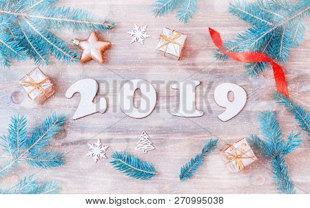 New Year 2019 background - 2019 figures, Christmas toys, light blue fir tree branches and snowflakes. New Year 2019 festive seasonal still life