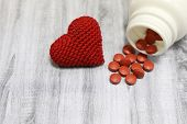 Pills and red knitted heart on wooden table. Concept of antidepressants, hypertension, heart disease, blood pressure poster