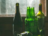 Several empty bottles of alcohol near the dirty window. Selective focus. Alcoholism, drunkenness, loneliness and depression concept poster