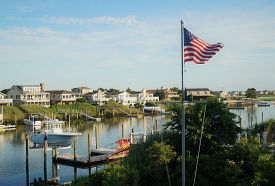 Avalon, New Jersey - July 18, 2014: An American Flag Waves In Front Of A Row Of Luxury Waterfront Be