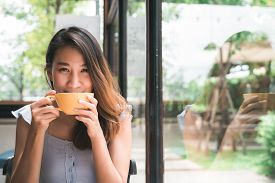 Cheerful Asian Young Woman Drinking Warm Coffee Or Tea Enjoying It While Sitting In Cafe. Attractive