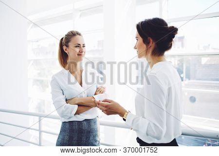 Two Female Employees Having Pleasant Conversation After Analyzing Strategy On Digital Tablet