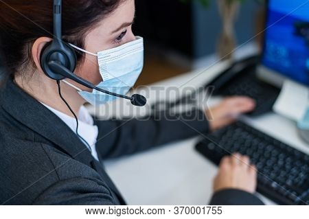 Close-up Of A Female Receptionist Wearing A Facial Mask Talking On A Headset While Sitting At A Work