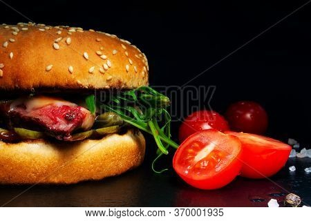 Burger With Chop, Steak, Cheese, Salad On A Black Background