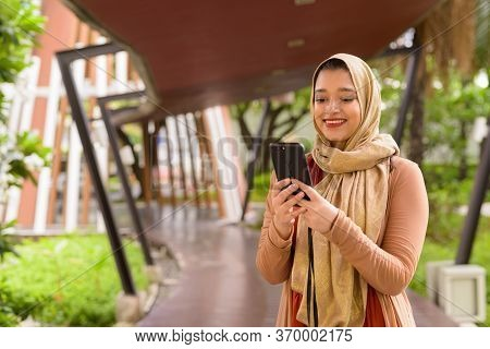 Happy Young Beautiful Indian Muslim Woman Using Phone In The City With Nature