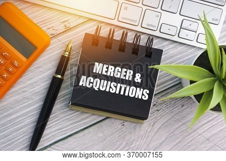 Merger And Acquisitions Text With Fountain Pen, Keyboard, Decorative Plant, Calculator And Notepad O
