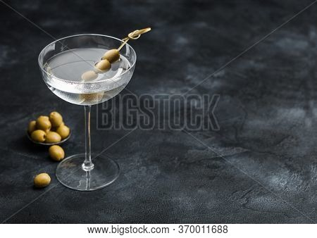Vodka Martini Gin Cocktail In Modern Glass With Olives In Metal Bowl And Bamboo Sticks On Black Back