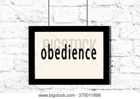 Black Wooden Frame With Inscription Obedience Hanging On White Brick Wall