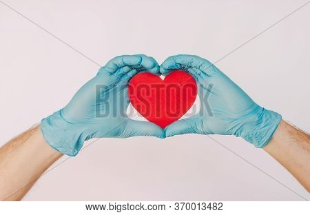 Closeup Man Doctor In Latex Protective Gloves Hold Red Heart Symbol In Hands Isolated On White Backg