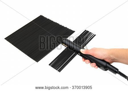 Creative Hair Straightening Concept. Female Passes Dry Black Spaghetti Through A Flat Iron. First Pe