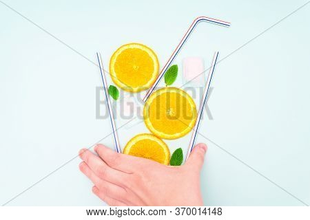 Creative Flat Lay Arrangement Of Orange Slices, Fresh Mint Leaves, Ice Cubes And Drinking Straws In