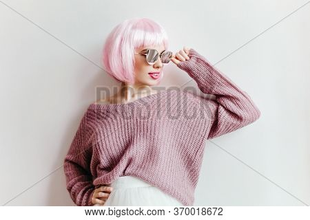 Confident Girl With Light-pink Hair Touching Her Glasses With Smile. Indoor Photo Of Good-looking Yo