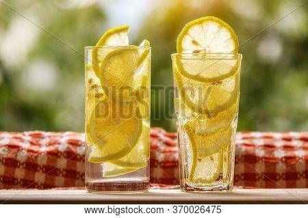 Glasses Of Lemonade With Lemon On The Sunny Garden Background.