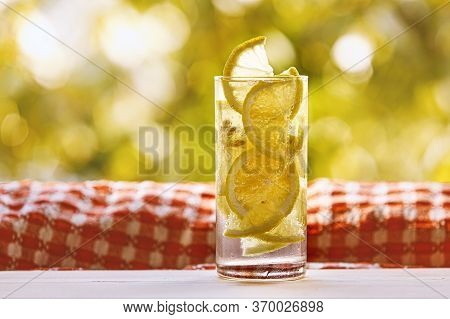 Glass Of Lemon Water On The Sunny Garden Background.