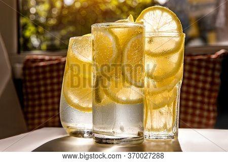 Glasses Of Lemonade With Lemon On The Sunny Background.