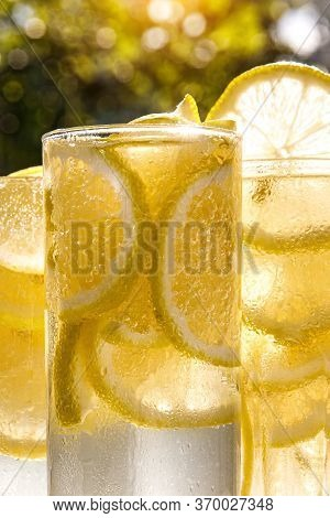 Glasses Of Lemon Water On The Sunny Garden Background. Close-up View.