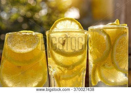 Glass Of Lemon Water On Sunny Garden Background.