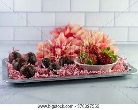 Chocolate Covered Strawberry Cake Balls Arranged On A Rustic Metal Tray With Pink Paper Shreds And A