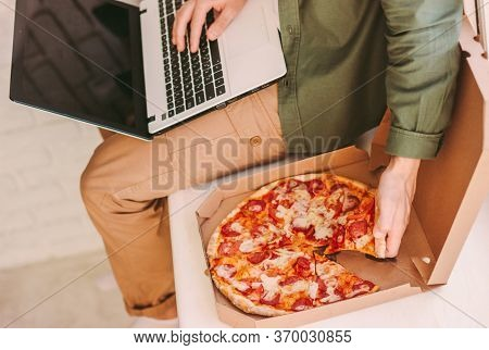 Top View Hungry Businessman Eating Tasty Italian Pizza, Using Laptop Work Distance Work From Home Of
