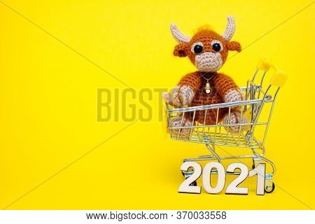 The Bull Is The Symbol Of The New Year 2021. Knitted Toy Bull In A Supermarket Toy Cart On A Yellow