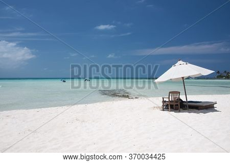 Sunny Summer Morning On The Beautiful White Sand Beach With A Chaise Lounge And Umbrella On The Shor