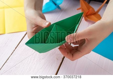 A Girl Plays With An Origami Toy That She Made Herself. Origami Boat Made Of Colored Paper