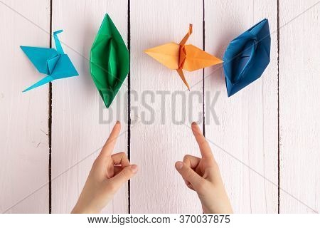 The Girl Points Her Fingers At The Origami Of Colored Paper That She Made Herself. Origami On The Ta
