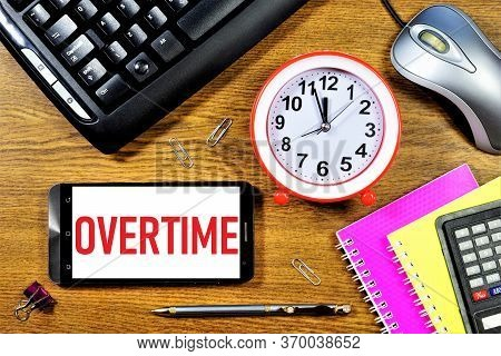 Overtime-text Inscription On The Smartphone Screen. The Employee's Desktop Contains A Clock, A Compu