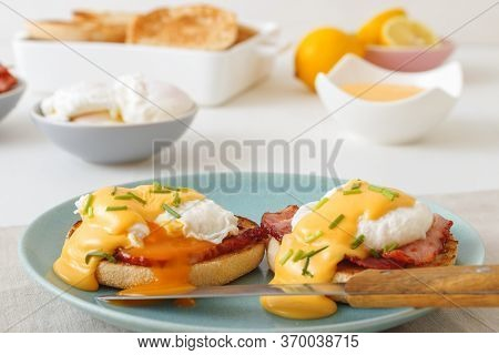 Eggs Benedict, English Muffins, Grilled Ham, Poached Eggs, Hollandaise Sauce, Chive Herbs, Lemon, Cu