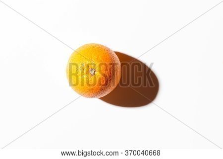 Fresh Juicy Orange On A White Background With A Hard Shadow. Top View