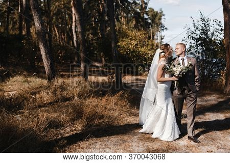 Bride In The Wedding Dress And Veil And Groom In Checkered Suit Walking In The Pine Forest. Bride An