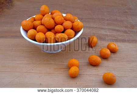 Plateful Of Organic Coated Peanuts And Spilled Coated Peanuts On Wooden Background