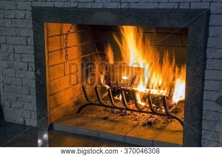 Burning Firewood In A Home Fireplace, Bright Flames, A Symbol Of Warmth And Comfort In The House