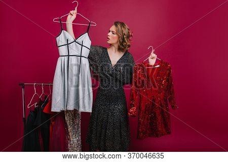 Serious Short-haired Girl Spending Time At Shopping, Choosing Attire For Photoshoot. Indoor Portrait