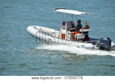 Middle Aged Couple Leisurely Cruising On Biscayne Bay Off Of Miami Beach,florida In A Pontoon Fishin