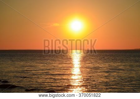 Bright Sunset Over The Lake. Yellow Sun. Sunny Path In Calm Water. Red-orange Sunset. Black Stones I