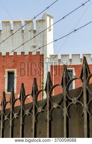 Tower Of A Historic Building Behind An Iron Rusty Fence With Peaks And Barbed Wire Against A Clear B