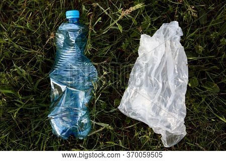 Closeup Portrait Of Plastic Bag And Plastic Used Bottle, Rubbish In Meadow, Trash In Field, Ecologic