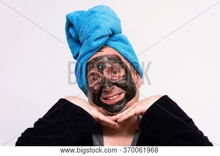 A Fun Concept Of Cosmetology. A Funny Fat Man With A Black Cream Mask On His Face, In A Dressing Gow