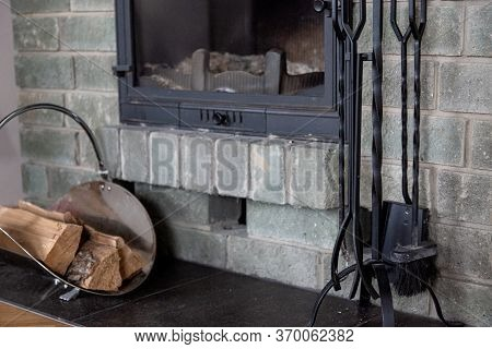 Close-up Gray Brick Wall Fireplace. Cast-iron Fireplace Accessories And Firewood In A Metal Basket N