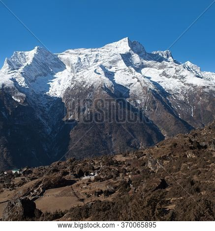 Panoramic View Of Kangtega And Thamserku Mountains And Buddhist Chorten With Prayer Flags On The Way