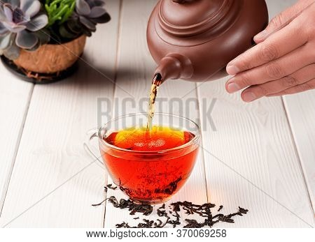 The Process Of Brewing Tea, Tea Ceremony. From A Clay Teapot, Red Tea Is Poured Into A Glass Cup. Fr