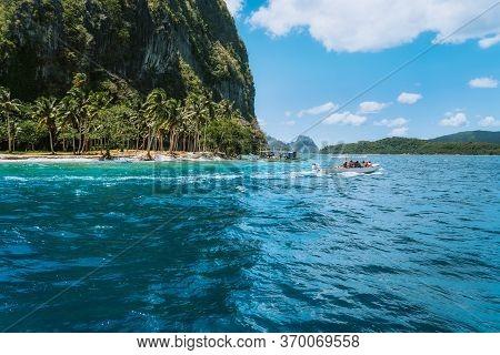 Boat With Tourists On Ipil Beach Of Exotic Island On Hopping Tour, Bacuit Archipelago, El Nido, Pala
