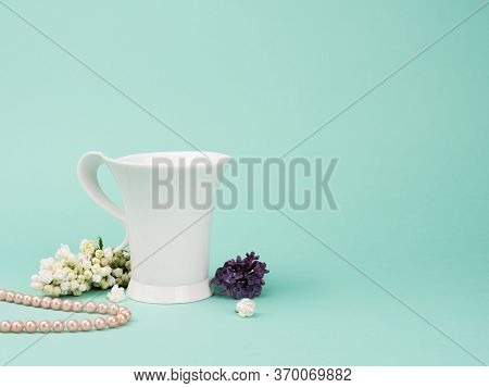 The Elegant White Cup, The Lilac And The Pearls On Turquoise Background.