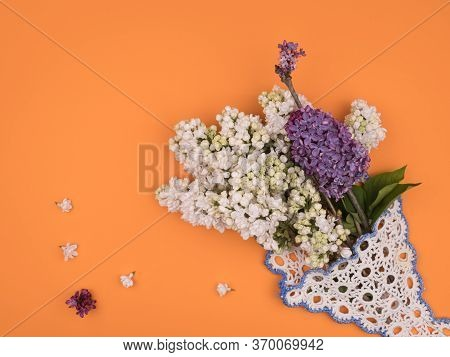 Bouquet Of Spring Flowers On An Orange Background. White And Purple Lilacs.