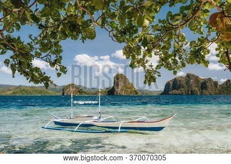 Banca Boat In Shallow Blue Water On Ipil Beach Of Pinagbuyutan Island, El Nido, Palawan, Philippines