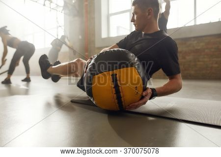 Sportive Man Using Exercise Ball While Having Workout At Industrial Gym. Group Training, Teamwork Co